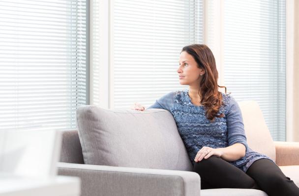 Nainen istuu sohvalla ja katsoo ulos ikkunasta, jossa on sälekaihdin.